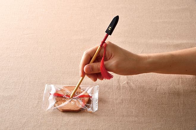 写真:鉾で瓶型のせんべいを割る様子